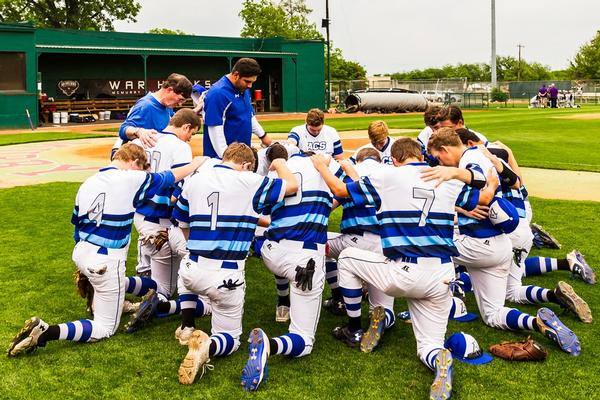 Baseball team praying together